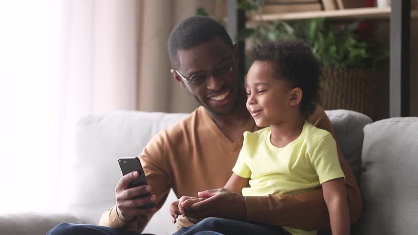 Happy african american dad and little son laughing looking at phone, black father teaching child boy using smartphone apps sitting on sofa, loving daddy holding cellphone talking to small kid at home Royalty-Free Stock Footage #1028900060