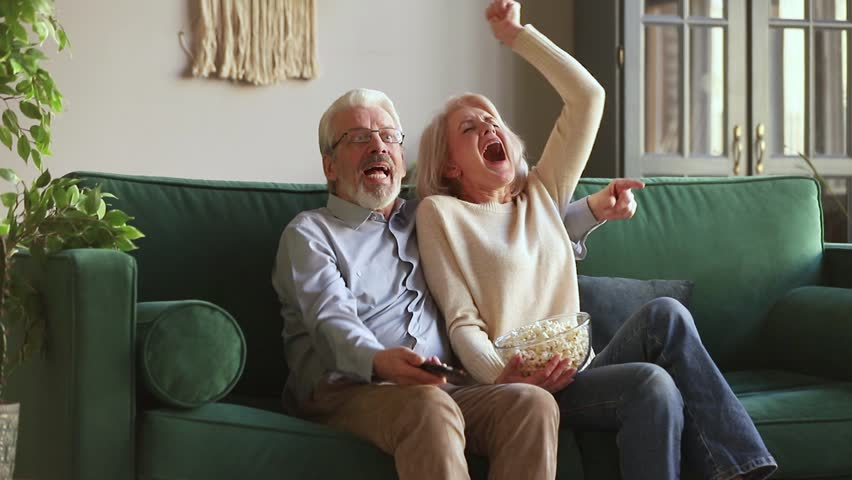 Overjoyed old mature couple football fans watching sport tv game support cheer winning soccer team sit on sofa together, happy excited senior family celebrate victory goal score view television match