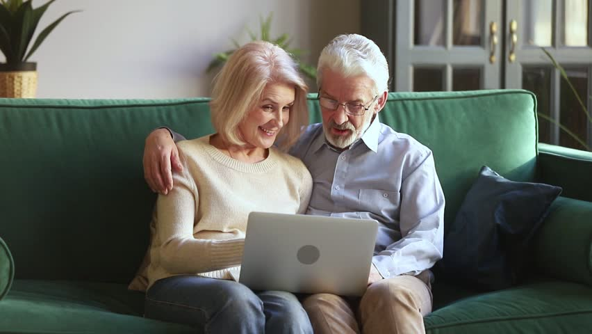 Happy senior aged couple talking embracing using laptop together reading discussing online news, elder mature old family man and woman looking at computer doing online shopping sit on couch at home