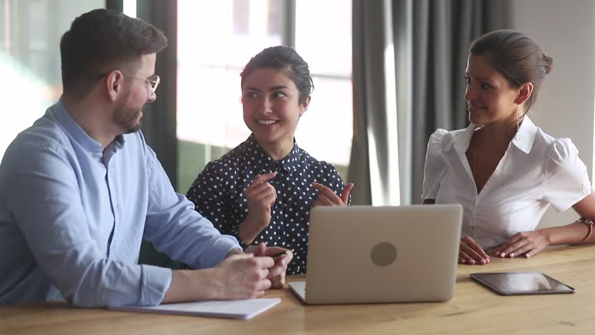 Young female indian leader sharing ideas with coworkers teaching interns sit with laptop, hindu business woman mentor coach talking to employees trainees explaining new project in teamwork discussion Royalty-Free Stock Footage #1028900225