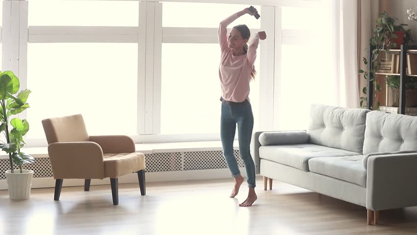 Happy carefree young woman dancing alone in modern living room with big window listen to music on smartphone, funky millennial girl holding phone enjoy new hit song playing in app having fun at home | Shutterstock HD Video #1028900228