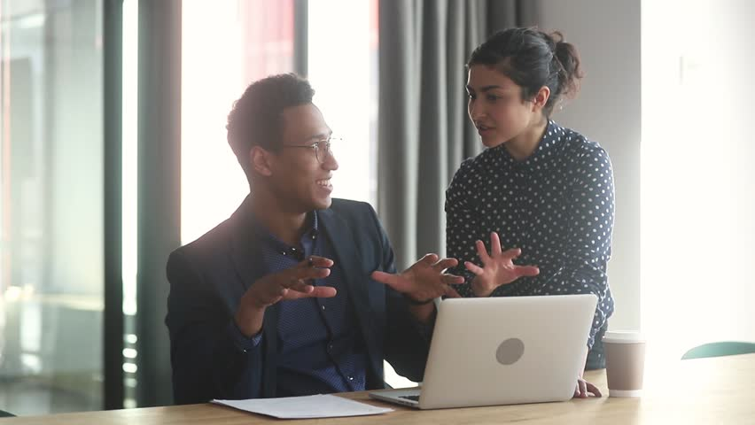 Indian female professional mentor coworker helping african intern new employee explain computer work at workplace, diverse leader and worker discuss online project in office, apprentice and mentoring Royalty-Free Stock Footage #1028900252