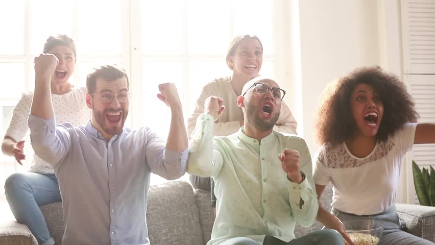 Overjoyed multicultural friends group football fans watching sport tv game sit on couch together, diverse happy people excited by goal score scream celebrate victory support cheering winning team