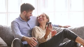Happy millennial couple talk laugh looking at smartphone using funny apps sit on couch, smiling man and woman relaxing at home having fun in social media on cellphone online watching video on phone