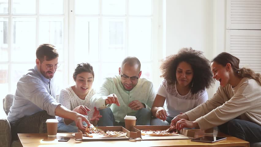 Happy diverse friends group having fun eating pizza together share dinner meal at home or in dorm, multicultural hungry young people students laughing talking during lunch food at party meeting
