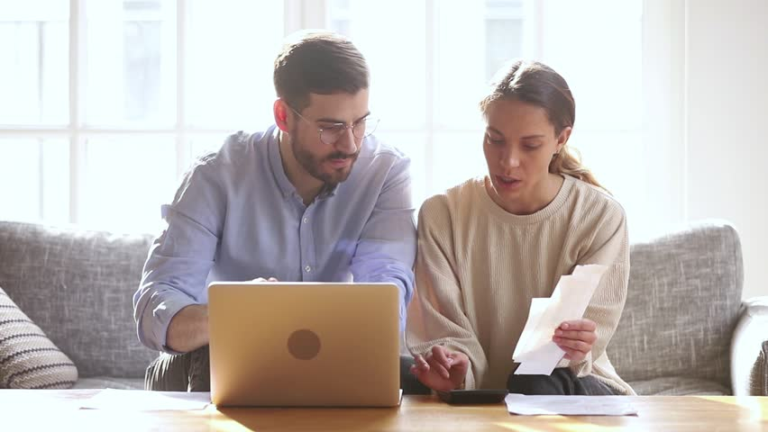 Serious millennial couple calculating domestic paper bills at home with laptop computer paying online, focused family man and woman planning budget, managing bank loan payments, household economy Royalty-Free Stock Footage #1028900348