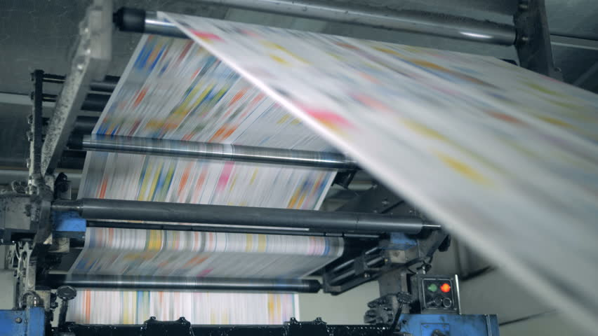 A machine works, rolling printed newspaper in typography facility. Royalty-Free Stock Footage #1028905658