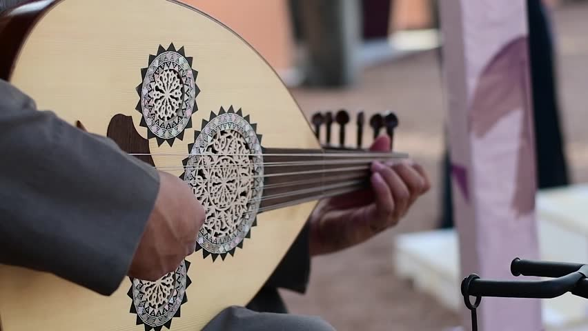 Arabic musician from Saudi Arabia plays music on traditional instrument from Middle East called Oud or Ud.
