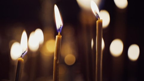 Candles flame brightly in the church. Burning candles on the blurred background with light spots. Close-up