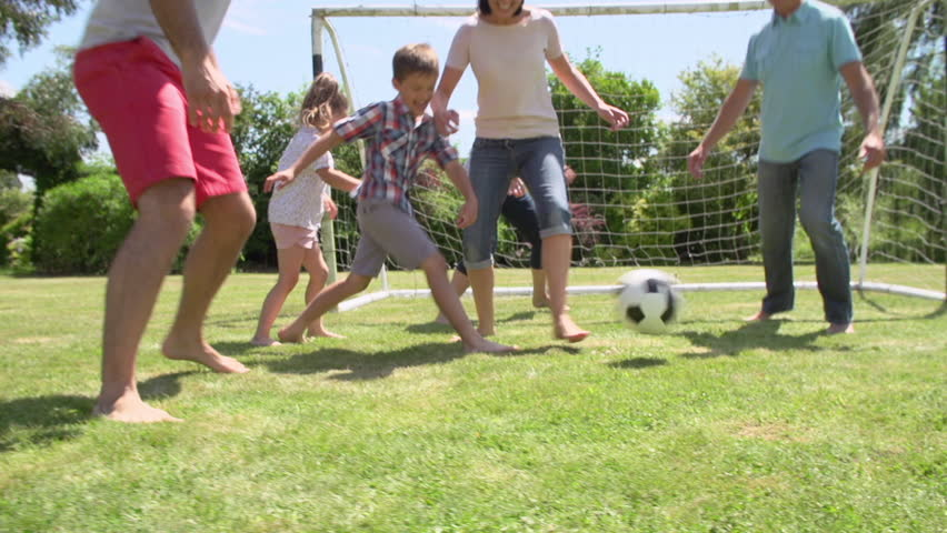 Multi-generation family playing football in garden together.Shot on Sony FS700 at frame rate of 25fps