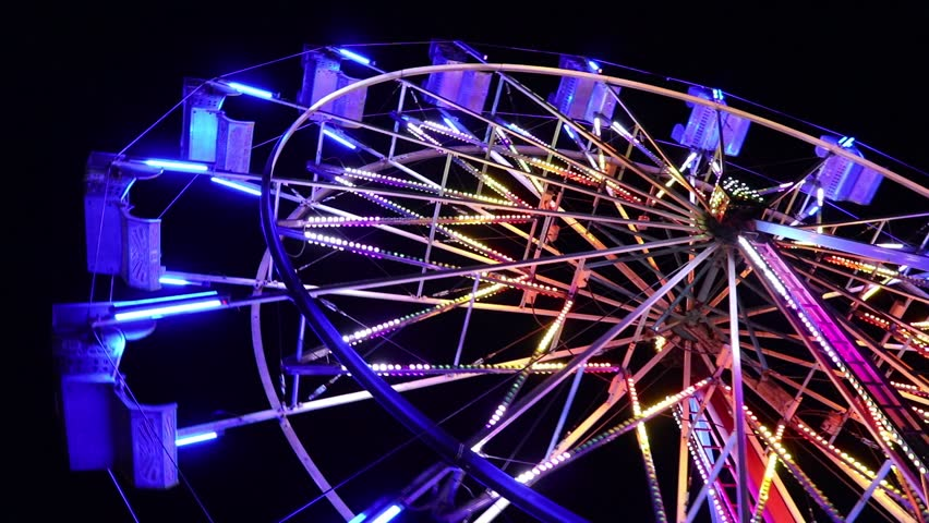 Brightly lit ferris wheel ride spinning at night at a carnival, amusement park, theme park, fair, thrill park. | Shutterstock HD Video #1028933708