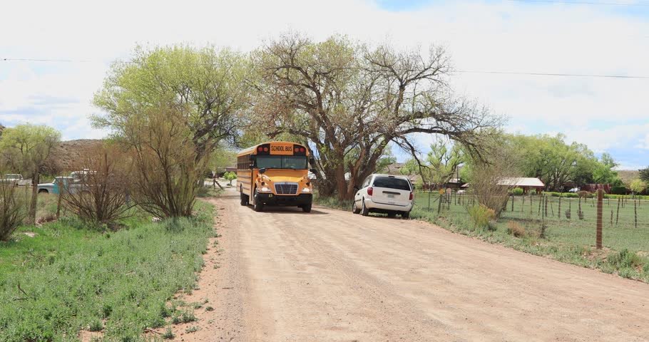Chinle, AZ/US- 04-25-2019: The infield school bus passing by a rural area.