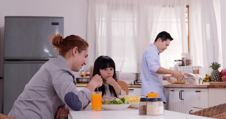 Asian gay couple and daughter dining in their kitchen together. Gay couple take care little girl at home. | Shutterstock HD Video #1028939906