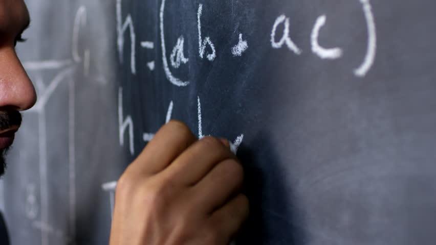 Handheld tracking shot with close up of male university professor writing math formula on chalkboard   Shutterstock HD Video #1028944226