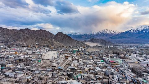 4K Timelapse of cityscape and high snow mountain range on rural desert landscape and Leh Palace with beautiful blue cloudy sky and amaizing cloud moving as background, viewed of rooftop Leh, India