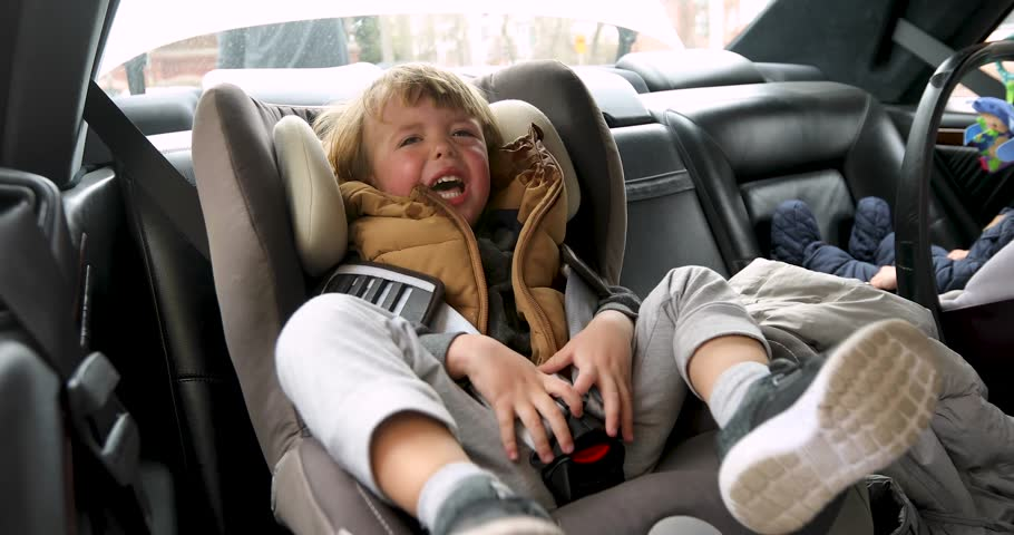 Closeup crying boy with worried stressed expression in child safety seat in car interior