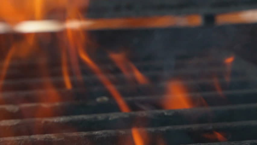 Tasty meat for a burger falls on a barbecue grill. Fire is burning and juicy steak with stripes are become to be ready. Close up of chief cooked tasty burger in casual bar