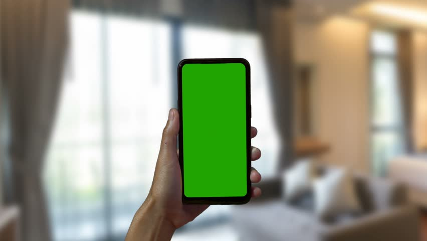 Close-up of a Woman's Hand Holding Green Mock-up Screen Smartphone. Modern Mobile Phone. In the Background Cozy Living Room or Home Office.  | Shutterstock HD Video #1028986976