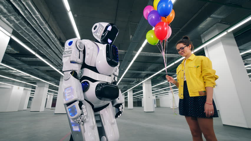 Smiling girl is giving colourful balloons to a cyborg | Shutterstock HD Video #1028988323