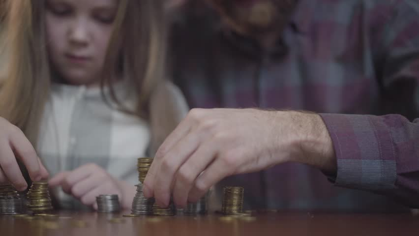 Unrecognizable man in shirt and little concentrated girl sitting at the table counting coins close up. Father and daughter making stacks from coins. The dad teaching kid economy. Money saving concept | Shutterstock HD Video #1029001871