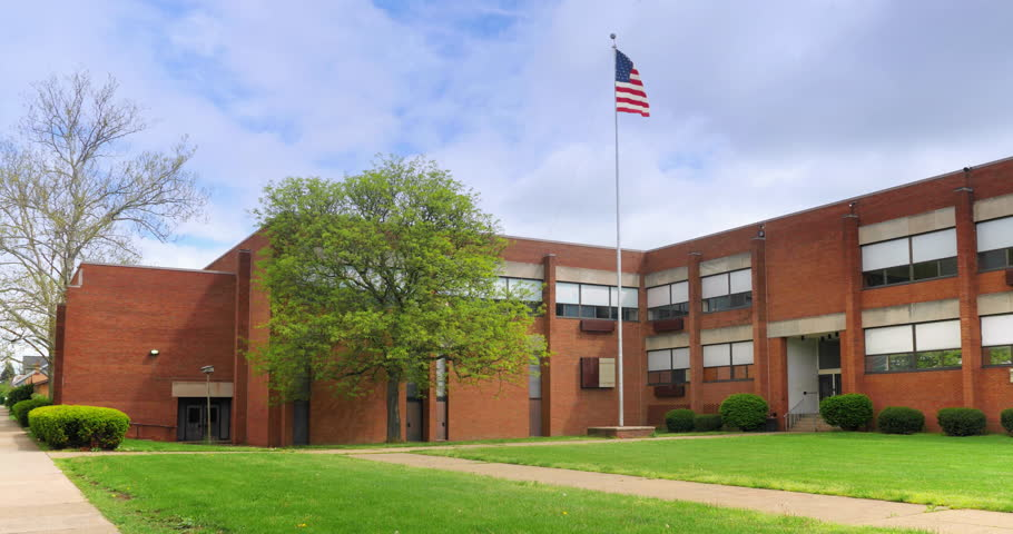 A daytime Spring establishing shot of a typical two-story red brick school building in a small midwestern Pittsburgh suburban town. Winter Summer Night matching available. Night: 1067665853