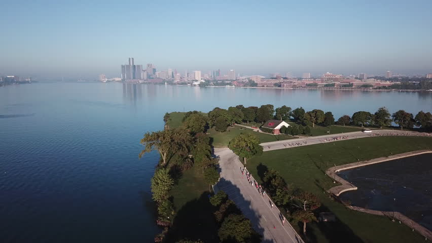 View of the Detroit skyline from Belle Isle on the Detroit river. Lake freighter passing by on a sunny summer day with blue sky. Aerial drone video of Michigan.