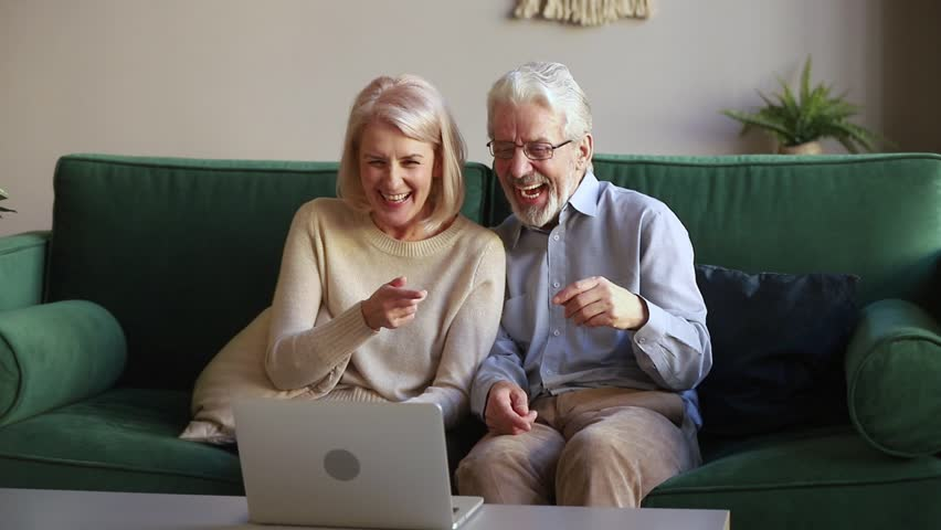 Happy senior old couple laughing talking making distance video call looking at laptop webcam sitting on sofa, cheerful mature aged family enjoy online chat internet conversation on at home
