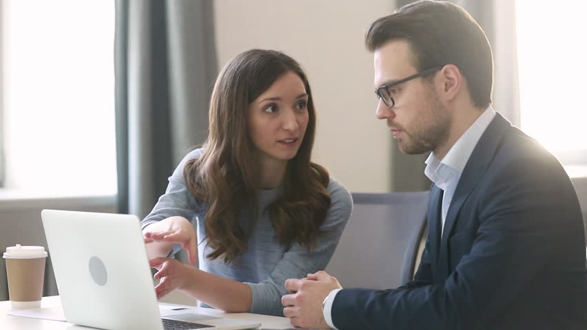 Female manager insurer consulting male customer with laptop at meeting, young saleswoman or mentor showing online presentation of deal benefits talking convincing client teaching intern sit at desk | Shutterstock HD Video #1029051425