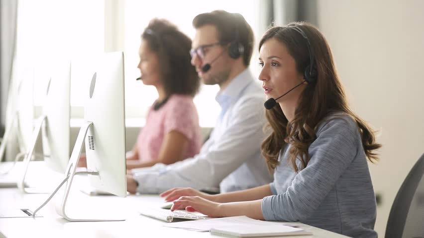 Young woman customer care support service agent call center operator in wireless headset talk consult online client using computer solving complaints on helpline or sell services in telesales office Royalty-Free Stock Footage #1029051440