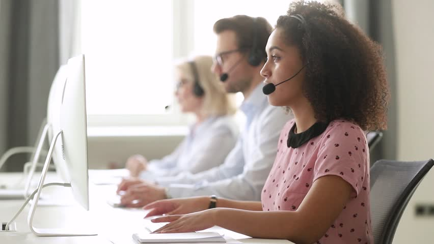 Serious african female call center agent wear wireless headset using computer looking at screen consulting customer with online problem, focused black woman operator working in support service office