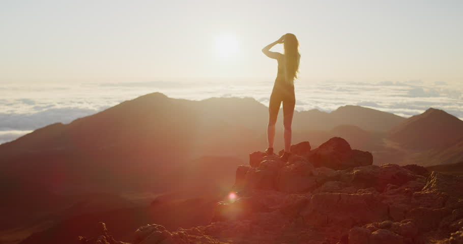 Young athletic woman looking out toward an epic sunrise on the top of a mountain, epic outdoors fitness lifestyle #1029056189