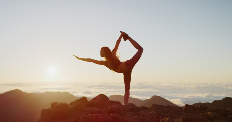 Young athletic woman performing yoga pose on the top of a mountain at sunrise, zen wellness woman performs dancer's pose