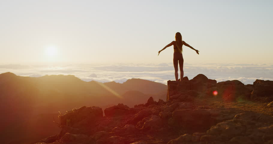 Beautiful young woman performing a spiritual yoga pose on the top of a mountain at sunrise in slow motion, sunrise zen wellness #1029056216