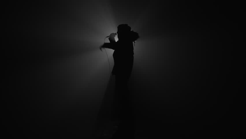 Silhouette of rapper performing with microphone