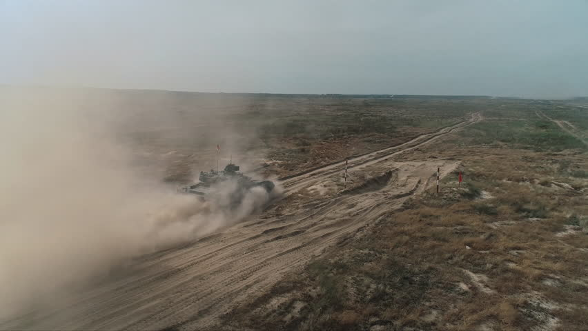 Aerial View Military Army Tank Shooting. Heavy Combat Fighting Vehicle Training in Sand Back View. Battlefield Advanced Technology/ Drone Shot Footage 4K (UHD)