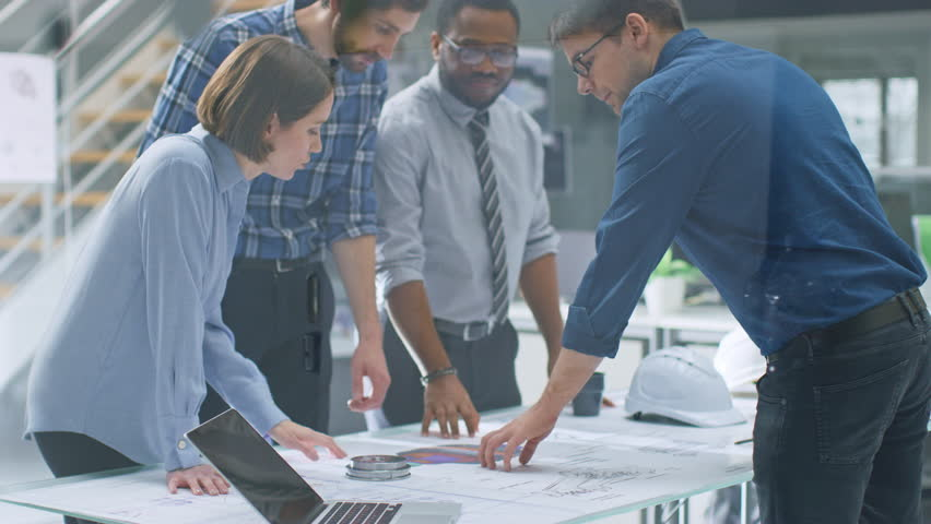 In the Industrial Engineering Facility: Diverse Group of Engineers, Technicians, and Specialists on a Meeting, Have Discussion, Analyse Engine Design Technical Drafts that are Lying on the Table   Shutterstock HD Video #1029098120