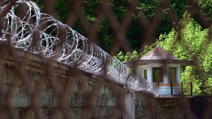 View of guard tower and razor wire at a prison or jail through the prison fencing.