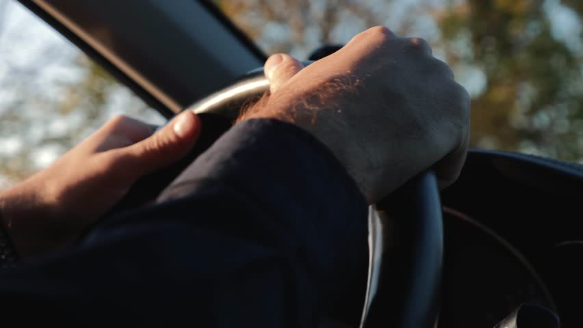 Large male hands on the steering wheel of the car. Driving a car. Journey.Business. | Shutterstock HD Video #1029122018