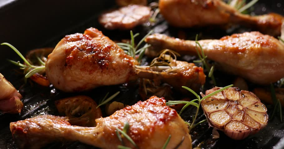 Grilled chicken. Grilled chicken legs, drumsticks with addition garlic, lemon and rosemary on grill plate. Grill food, 4K