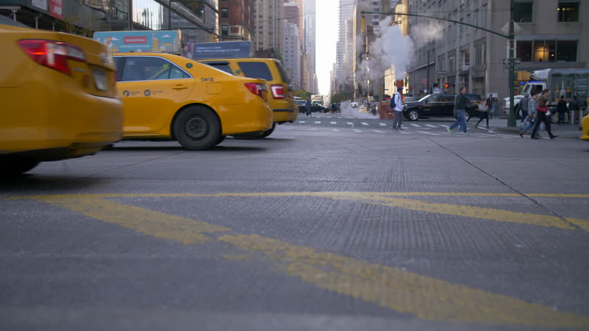 NEW YORK CITY, USA - 03/08/2019: New York city traffic commuting at rush hour. Slow motion Classic Yellow Taxi Cabs passing with Tourist and commuters walking on the sidewalk with smoke rising.
