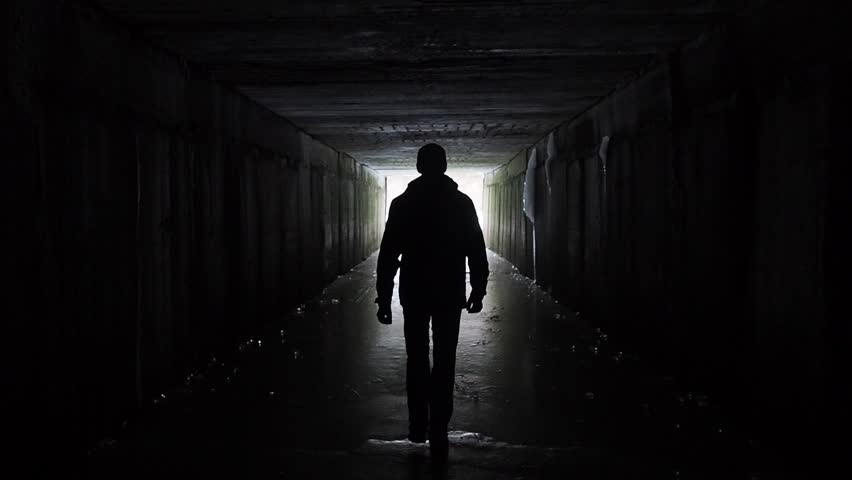 Man silhouette walking in a dark tunnel. Underground, post apocalyptic view. Exit and depression concept. People authentic video. Depression caused by coronavirus, quarantine, COVID 19. Human health  | Shutterstock HD Video #1029169520