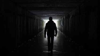 Man silhouette walking in a dark tunnel. Underground, post apocalyptic view. Exit and depression concept. People authentic video. Depression caused by coronavirus, quarantine, COVID 19. Human health