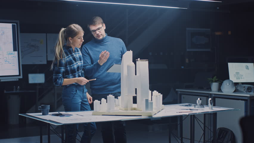In the Creative Architectural Bureau Two Professional Engineers Work on a Model of a City District. Urban Planners Work on a Functional Building Model. They Talk and Use Digital Tablet Computer Royalty-Free Stock Footage #1029170147