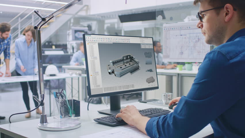 Engineer Working on Desktop Computer, Screen Showing CAD Software with 3D Component. In the Background Engineering Facility with Blueprints and Drawings with Industrial Design. Over the Shoulder | Shutterstock HD Video #1029171617