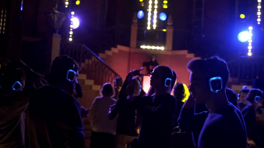 Moscow, Russia, November 2017, Happy young people are dancing and having fun at silent disco party in mansion interior. Nightlife. People listen and enjoy in music on headphones.