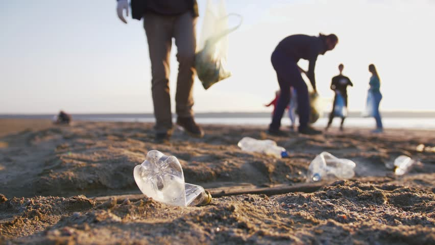Close up shot of young man picking up plastic bottles on the beach, slow motion #1029188840
