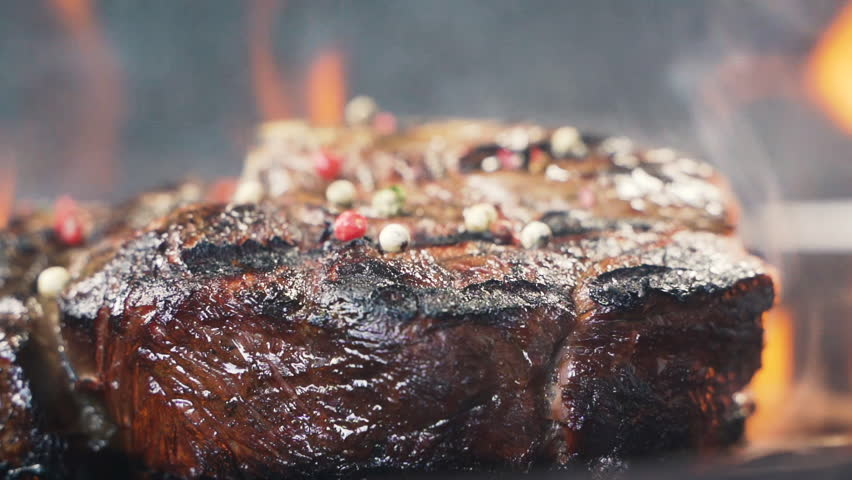 Close-up of spices fallen on steak. Large grains of pepper fall on tasty beefsteak, delicious juicy meat. Street food cooked on hot plate. Making a picnic. close up slow motion