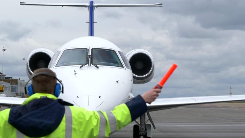 Airport Air Marshaller Signalling Executive Jet Pilot. Royalty-Free Stock Footage #1029193559