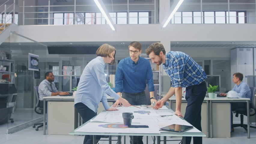 In the Industrial Engineering Facility: Female Designer Works with Industrial Engineer and Master Technician, They have Discussion, Analyse Engine Design Technical Drafts that are Lying on the Table   Shutterstock HD Video #1029209477