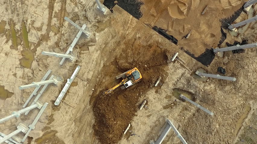 Aerial flight over new constructions site development where heavy machinery and construction workers are working with power tools in Eastern Europe, Lithuania, Alytus city outskirts. During cloudy day